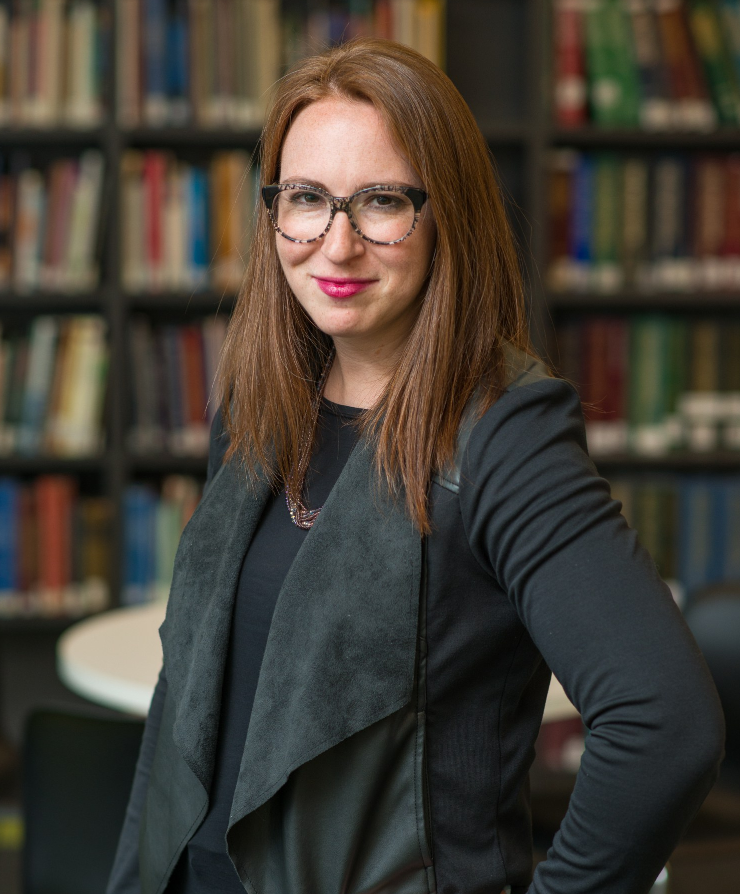 Image description: a redhead with black and white round glasses wearing a black shirt, black jacket, and a purple necklace poses in front of shelves of books. Photo courtesy of David Wolcheck.