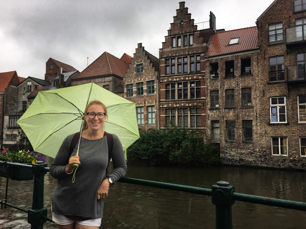 A smiling readhead with glasses and a lime green umbrella leans on a railing next to a canal.  Behind her are several brick buildings.