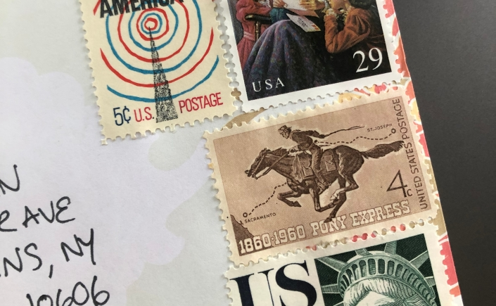 The right half of an envelope featuring four stamps: The Voice of America, Little Women, the Pony Express, and a statue of Liberty air mail