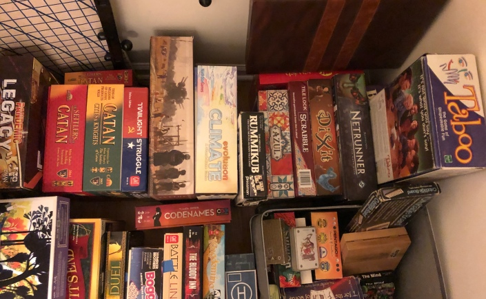 A photo of some of our board games on a closet floor.