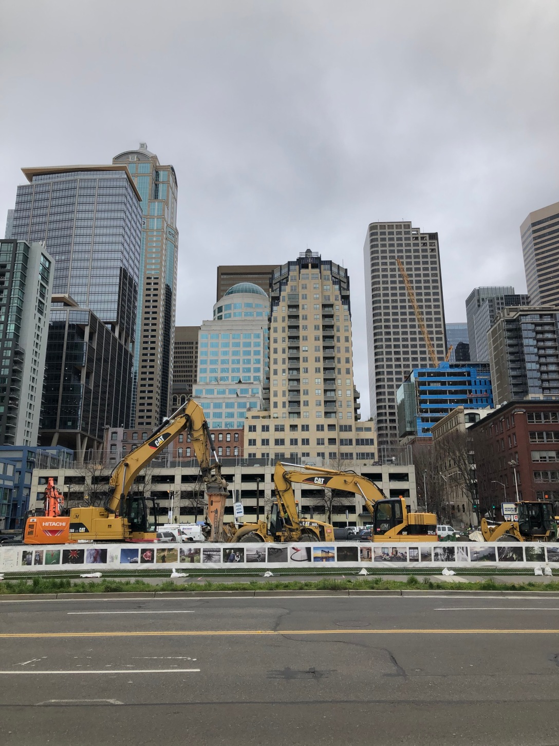 Many tall buildings behind construction equipment and a road