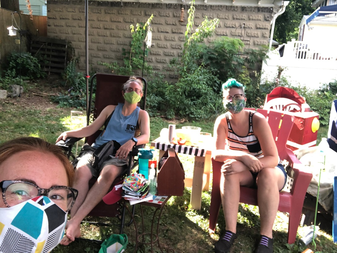Three women sit at distance wearing masks in a yard.