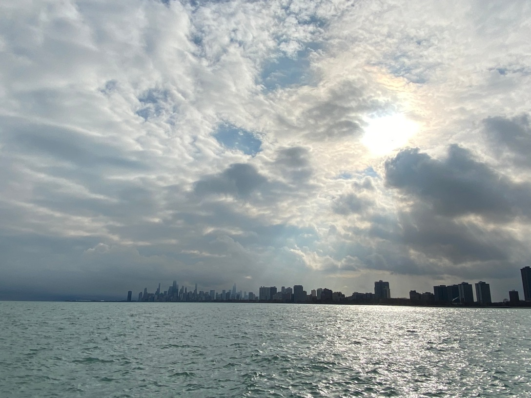 A big sky with many white clouds and the sun peaking through, creating sunbeams. On the horizon is the skyline of downtown Chicago, below which is Lake Michigan.